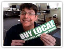 John from Websticker holds a Buy Local sticker to demonstrate importance of simple design