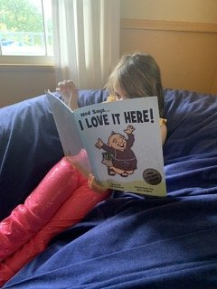 Young kid enjoys reading children's book, Ned Says, I Love It Here by Jeff Nicholson and Marc Hughes